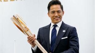 Tadahiro Nomura, tricampeón olímpico de judo, exhibe la antorcha...