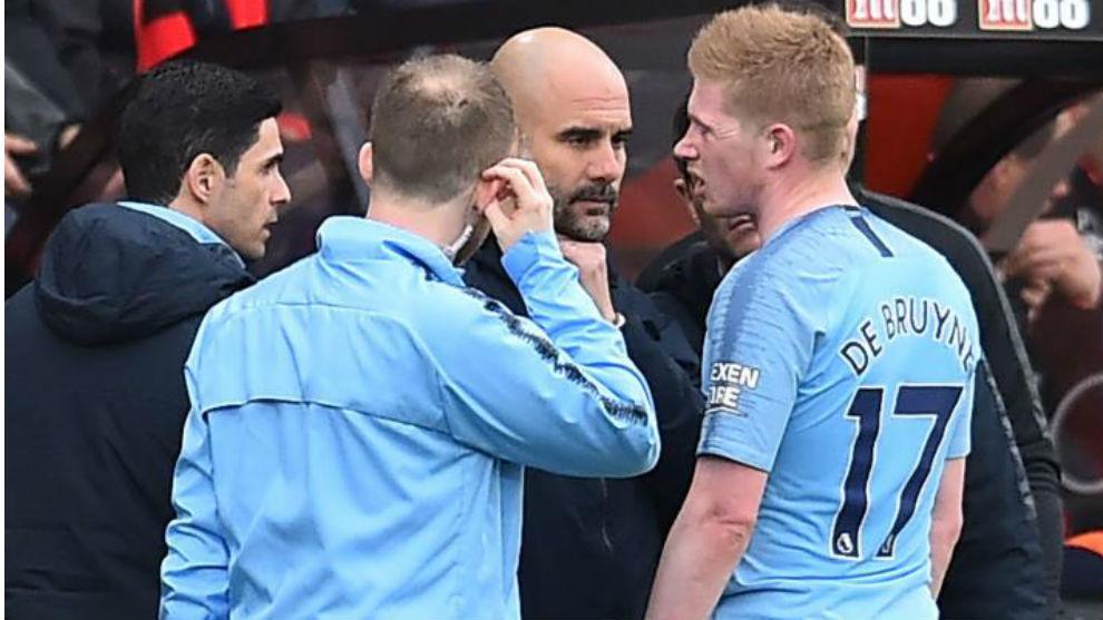 De Bruyne charla con Guardiola durante un partido.
