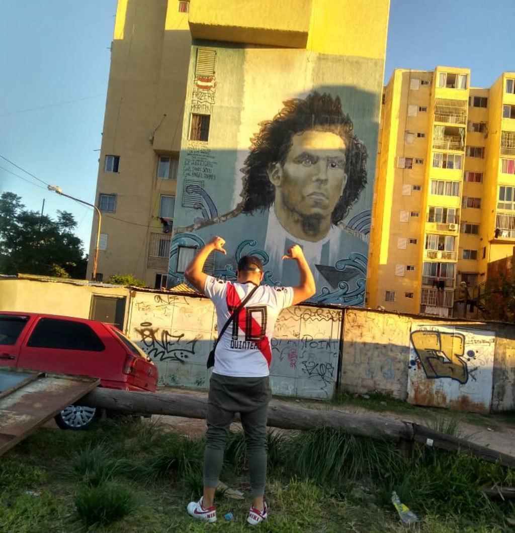Velázquez posa con la camiseta de River frente a un mural de Tévez...