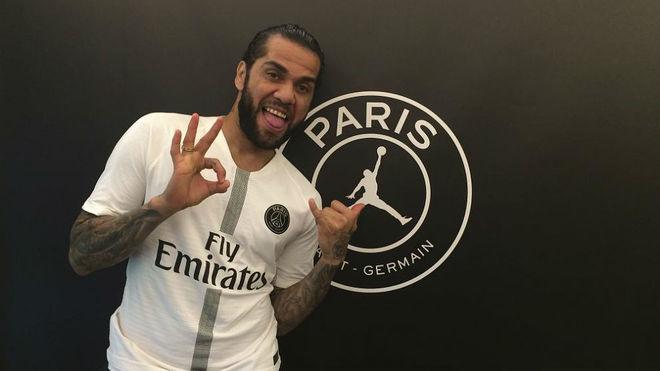 Dani Alves posa con la camiseta del PSG junto a su escudo.