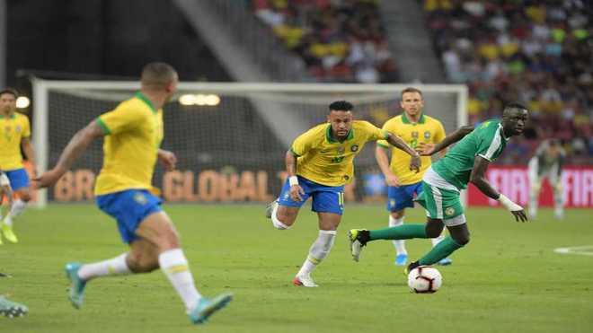 Neymar pasa la pelota ante la marca de un jugador de Senegal.