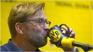 Jürgen Klopp bebe en una taza durante su etapa en el Dortmund.