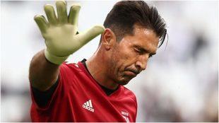 Buffon levanta la mano mientras cierra los ojos en un partido con la...