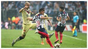 Guido Rodríguez, a la izquierda, disputa una pelota con Carlos...