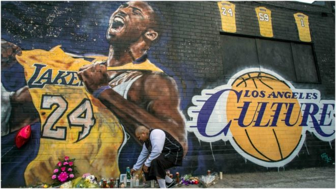 Una persona enciende una vela ante un mural con la imagen de Kobe Bryant.