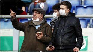 Hinchas de la Roma con el barbijo protector durante el partido con el...