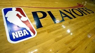 Un cartel de los playoffs de la NBA sobre el parqué de una cancha.
