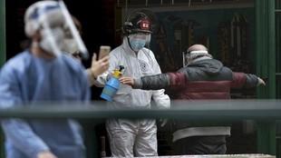 Personal de sanidad desinfecta a una persona.