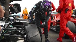 Lewis Hamilton examina la rueda reventada de su monoplaza, tras ganar...