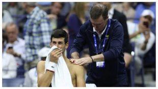 Djokovic es atendido por un médico durante un partido.