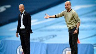 Guardiola da indicaciones en el Etihad ante la mirada de Zidane.