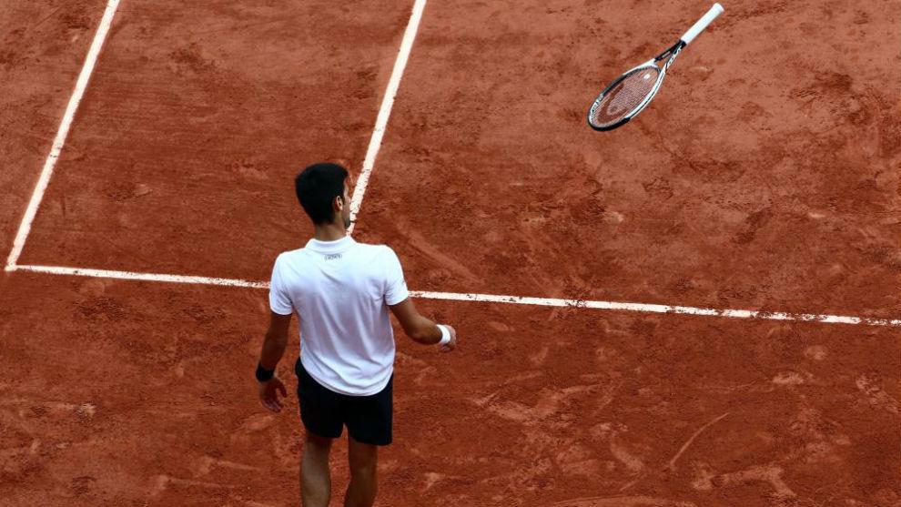 Djokovic lanza la raqueta durante un partido en tierra batida.