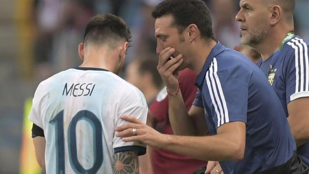 Lionel Scaloni da indicaciones a Leo Messi durante un partido.
