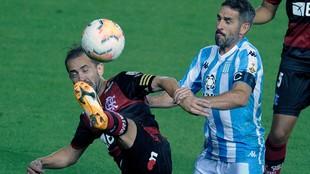 Lisandro López disputa la pelota con Everton Ribeiro.