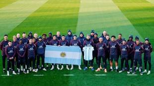 El plantel del PSG posan con una camiseta de Maradona y una bandera...