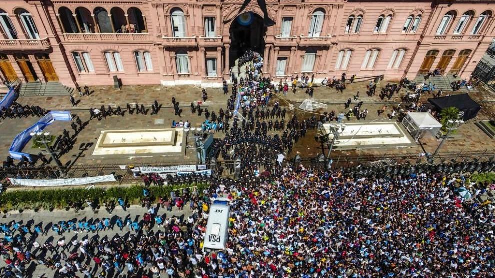 Una multitud de personas esperan para entrar a Casa Rosada para...