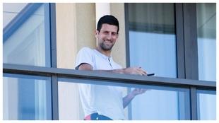 Djokovic sonríe desde el balcón de su habituación.