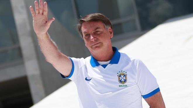 Bolsonaro saluda con la camiseta de Brasil.
