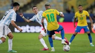 Neymar (29) pisa el balón ante la oposición de dos rivales en la...